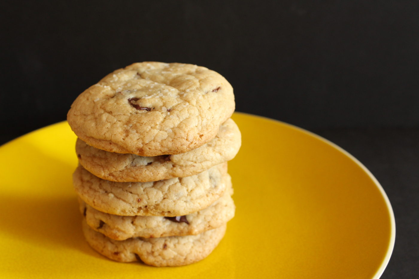 Chocolate chip cookies on yellow plate.