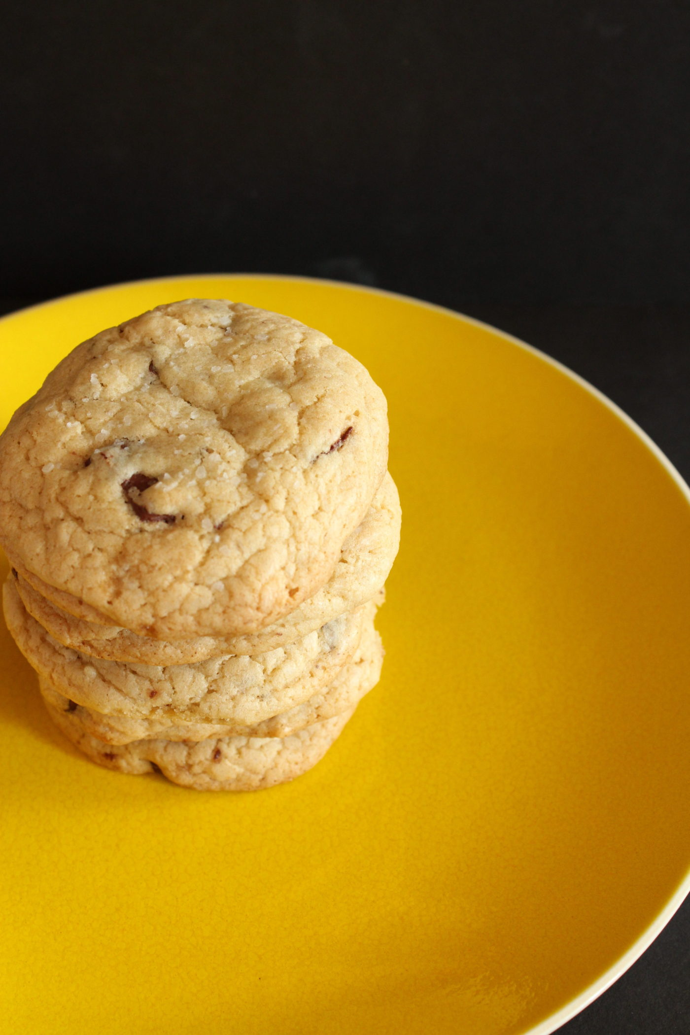 Chocolate chip cookies stacked on yellow plate